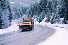 Photo of snow removal equipment working on a mountain road.