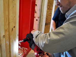 Electrical contractor drills into 2x4 to install electrical wiring