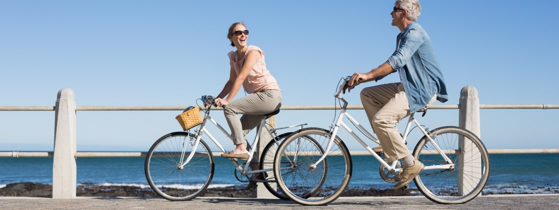Photo of couple riding bikes by the ocean